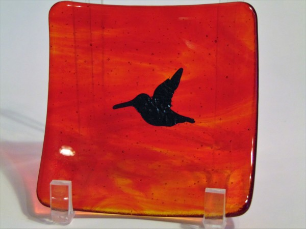 Small plate with copper hummingbird on red/orange streaky
