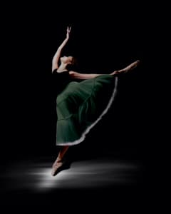 Arabesque Ballerina in Green Romantic Tutu on Black Background