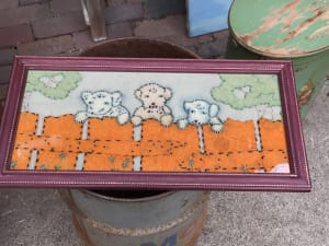 Framed felt picture of Puppies at a fence